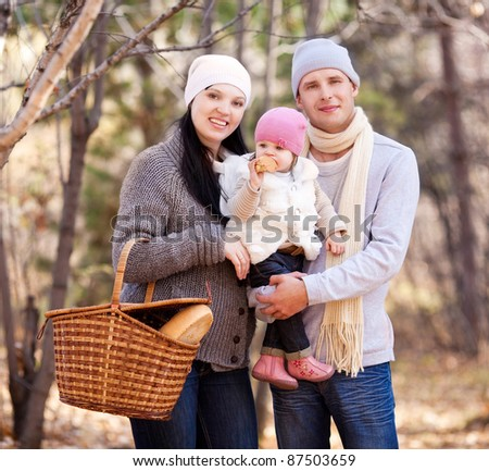 happy young family with their daughter spending time outdoor in the autumn park (focus on the baby) - stock photo