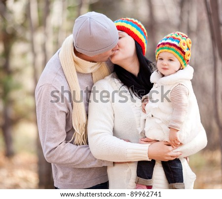happy young family with their daughter spending time outdoor in the autumn park (focus on the child)
