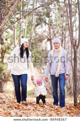 happy young family with their daughter spending time outdoor in the autumn park (focus on the man and woman) - stock photo