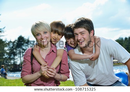 happy young family with their kids have fun and relax outdoors in nature with blue sky in background - stock photo