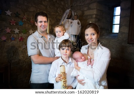 Happy young family with three children celebrating the baptism of their newborn baby - stock photo
