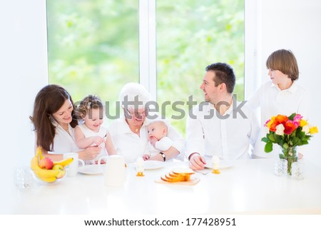 Happy young family with three children - teenager boy, toddler girl and newborn baby - having fun together during an Easter breakfast visiting their grandmother, in a white dining room with big window - stock photo