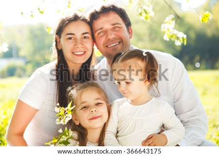 Happy young family with two children at the spring picnic