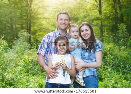 Happy young family with two children in the spring forest