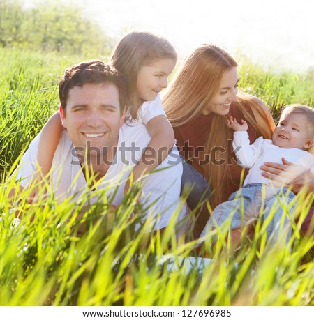 Happy young family with two children outdoors - stock photo