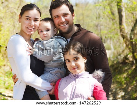 Happy young family with two daughters outdoors - stock photo