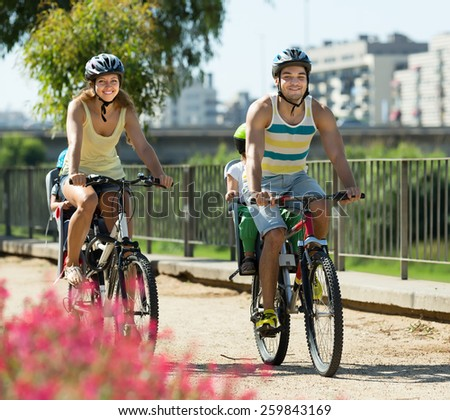 Happy young family with two little daughters traveling by bicycles. Focus on man