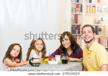 Happy young family with two little girls having breakfast together