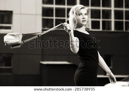 Happy young fashion blonde woman in black dress with handbag - stock photo
