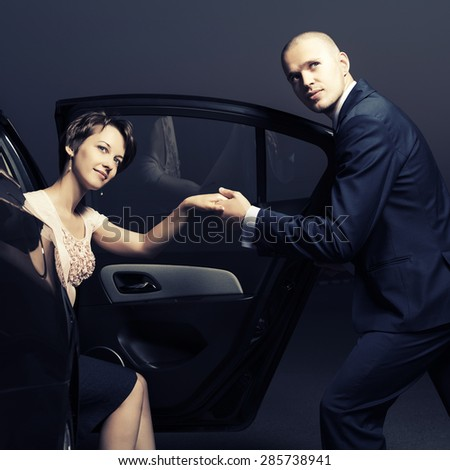 Happy young fashion couple in a car - stock photo