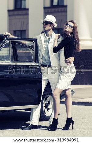 Happy young fashion couple in love by retro car - stock photo