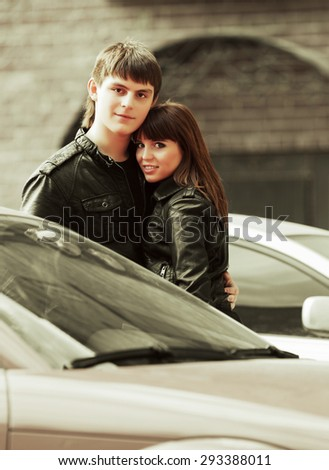 Happy young fashion couple in love next to car - stock photo