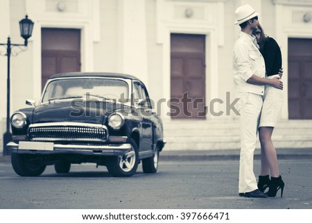 Happy young fashion couple in love next to retro car