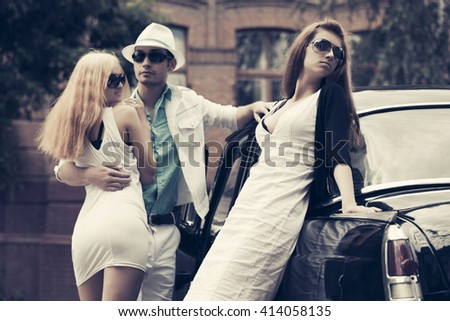 Happy young fashion couple in love next to retro car. Jealous girl. Male and female stylish model outdoor. Young man and woman in sunglasses on city street - stock photo