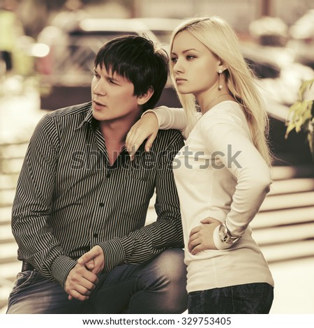 Happy young fashion couple in love on the city street - stock photo