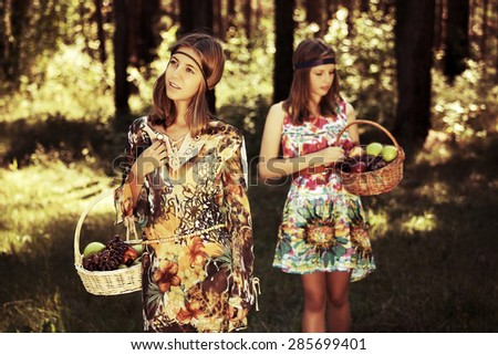 Happy young fashion girls with fruit basket walking in summer forest - stock photo