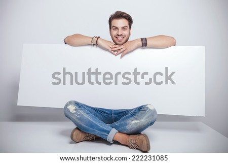 Happy young fashion man holding a big white board while sitting with his legs crossed. - stock photo