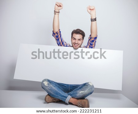 Happy young fashion man sitting with his legs crossed whith his hands in the air while holding a empty billboard.