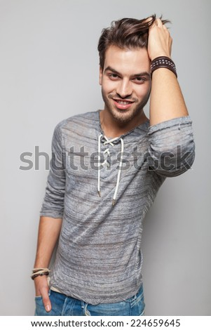 Happy young fashion man smiling and fixing his hair while holding his hand in pocket. - stock photo