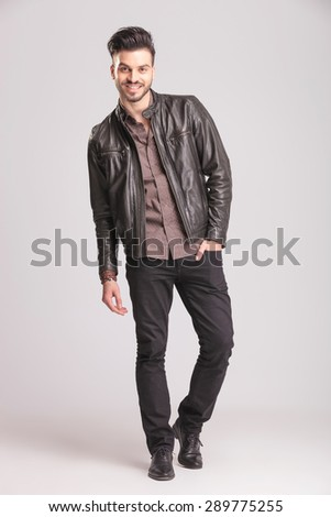 Happy young fashion man walking with his hand in pocket on studio background. - stock photo
