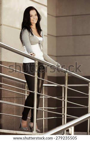 Happy young fashion woman at the wall - stock photo