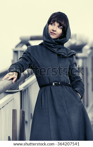 Happy young fashion woman in grey classic coat on the steps - stock photo