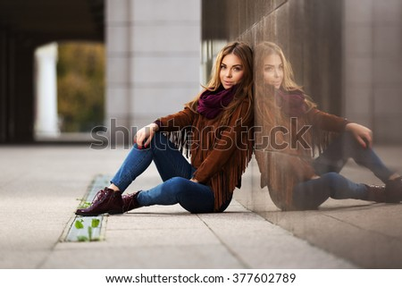 Happy young fashion woman in leather jacket sitting on city street - stock photo