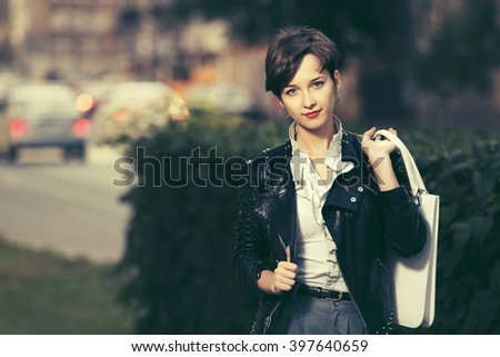 Happy young fashion woman in leather jacket with handbag  - stock photo