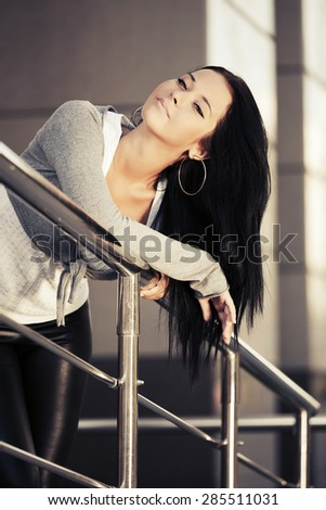 Happy young fashion woman leaning on handrail - stock photo