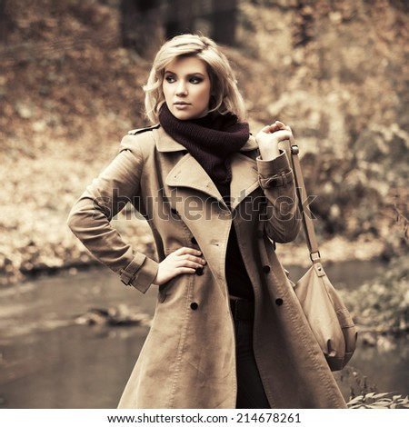 Happy young fashion woman with handbag in autumn forest - stock photo
