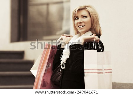 Happy young fashion woman with shopping bags at the mall window - stock photo