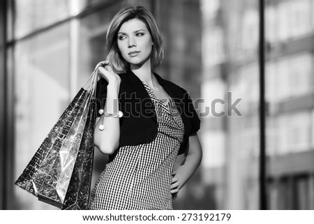 Happy young fashion woman with shopping bags next to mall windows