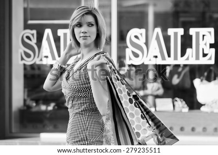 Happy young fashion woman with shopping bags next to mall windows  - stock photo