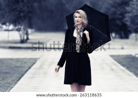 Happy young fashion woman with umbrella walking in the rain - stock photo