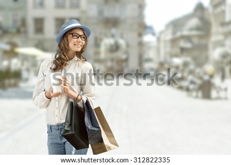 Happy young fashionable woman taking a coffee break after shopping, smiling with a coffee-to-go in her hands against urban background. - stock photo