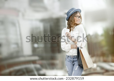 Happy young fashionable woman with bags having a coffee break after shopping and holding take away coffee against urban background. - stock photo