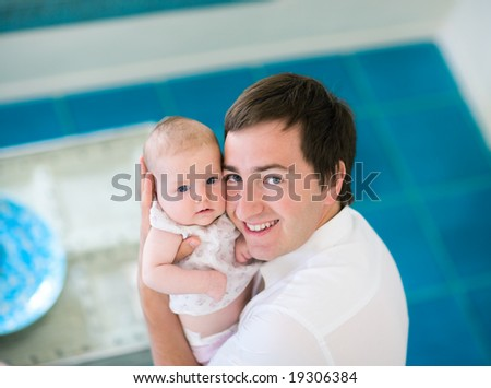 Happy young father and his baby daughter at home - stock photo