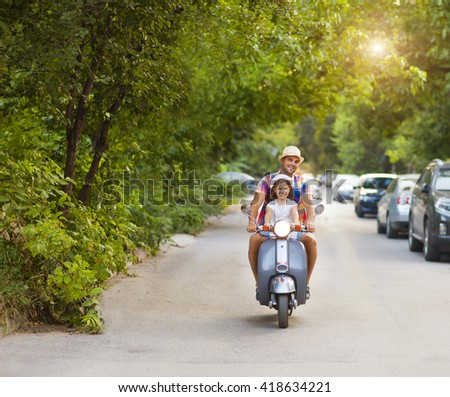 Happy young father and little daughter riding a vintage scooter in the street wearing hats. Holiday and travel concept - stock photo