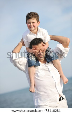 happy young  father and son have fun and enjoy time on beach at sunset and representing healthy family and support concept