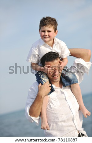 happy young  father and son have fun and enjoy time on beach at sunset and representing healthy family and support concept - stock photo