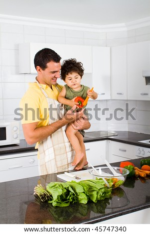 happy young father and son in modern kitchen - stock photo