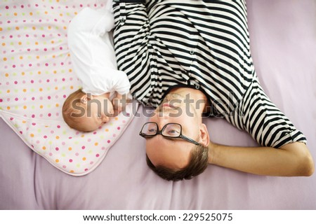 Happy young father enjoying special moments with his newborn baby daughter at home - stock photo