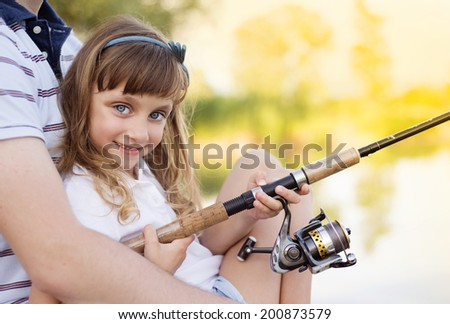 Happy young father fishing on the lake with his little daughter - stock photo