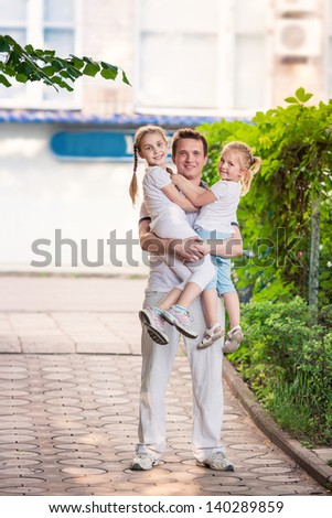 Happy young father holding his kids on hands outdoor - stock photo