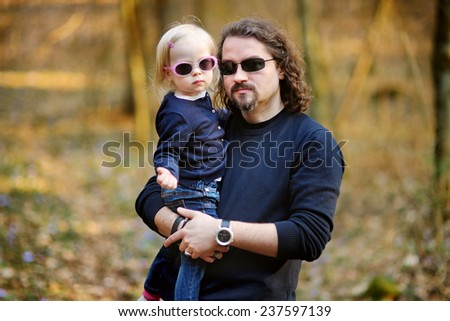Happy young father holding his little daughter on spring day outdoors - stock photo
