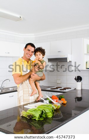 happy young father holding toddler boy in home kitchen