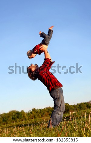 Happy young father is raising his young child up in the air over his head as they play outside on a sunny summer day. - stock photo