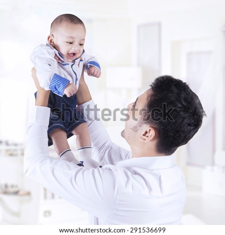 Happy young father lift up his baby boy in the bedroom while enjoying togetherness - stock photo