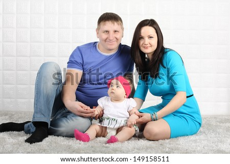 Happy young father, mother and baby sit on soft grey carpet.