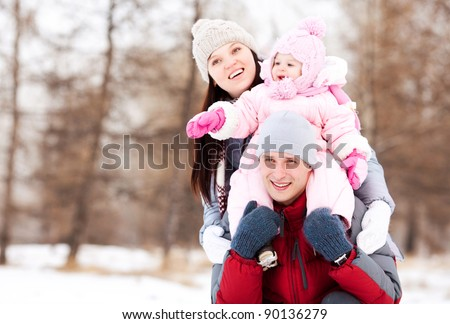 happy young father, mother and their daughter spending time outdoor in the winter park (focus on the man) - stock photo
